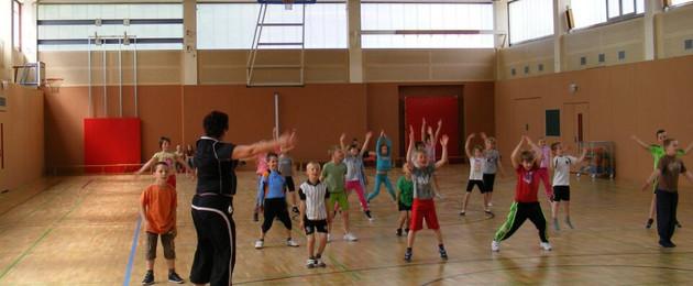 Kinder turnen mit Sportlehrerin in der Sporthalle An der Kotsche