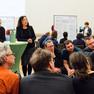 Eine Gruppe von Menschen sitzen in einem Kreis, der Moderator zeigt mit einem Tisch an die Moderationswand