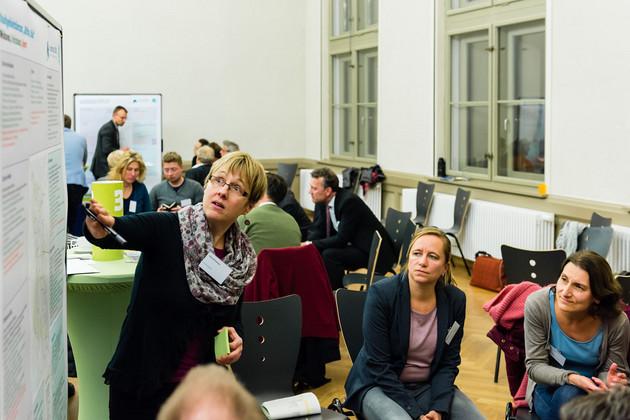 Die Moderatorin zeigt auf die Moderationswand, 2 Frauen blicken interessiert.