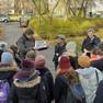 Eine Gruppe Menschen steht im Freien, ein mann erklärt etwas anhand einer Karte.