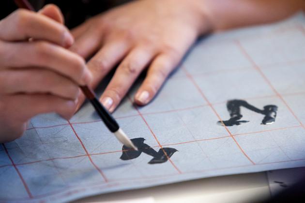 Kalligrafie Workshop: Chinesische Schriftzeichen werden mit einem Pinsel auf Papier aufgetragen