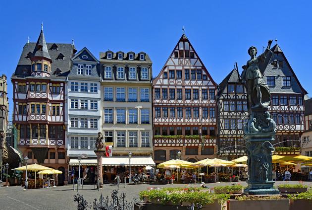 Häuserreihe in Frankfurt auf dem Römerberg. Im Ergeschoss Läden mit Arkaden, ab dem 1. Geschoss Fachwerkbau. Brunnen im Vordergrund