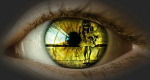 Nahaufnahme eines Auges. In der Reflektion ist schemenhaft eine Frau zu erkennen und eine geballte Faust