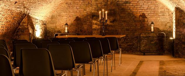 Beleuchteter Gewölbekeller mit Stuhlreihen und einem Tisch mit Kerzenleuchter
