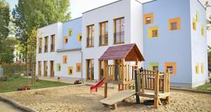 Gebäudeansicht Kita Salomonstraße 10: Blau-gelb angemaltes Gebäude mit Spielgerüst davor.