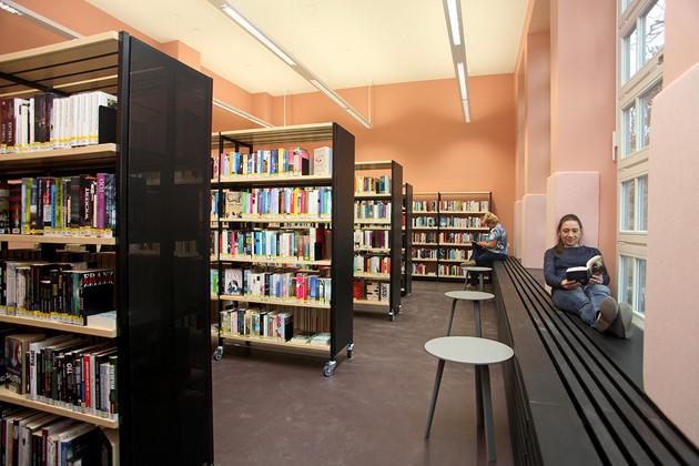 Belletristik in der Bibliothek Plagwitz, links Regale, rechts Fensterfront, eine Besucherin sitzt in der Fensterbank und liest