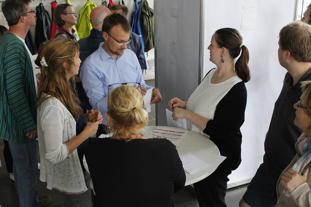 Eine Gruppe von Menschen steht an einem Stehtisch und füllt Projektsteckbriefe aus.