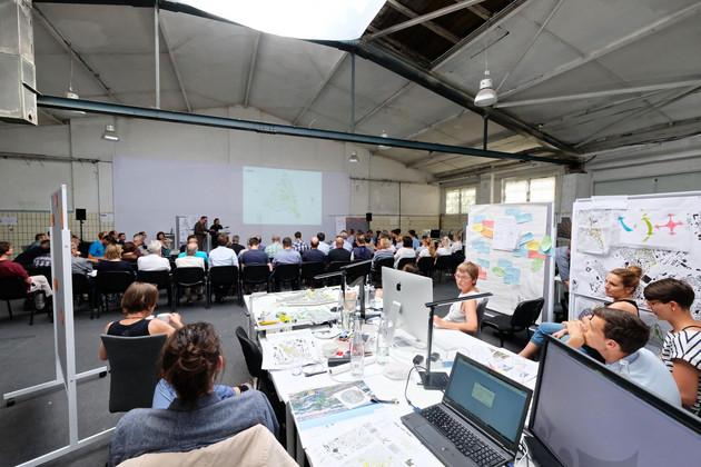 Eine Gruppen von Menschen hört einen Vortrag, dahinter sitzen Planer an Tischen und arbeiten