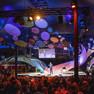 Moderator auf einer Bühne mit großem Publikum.