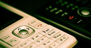 Nahaufnahme zweier Mobiltelefone, ein weißes und ein schwarzes im Hintergrund