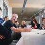 Eine Gruppe von Menschen um einen Tisch herum sitzend. Im Vordergrund links schauen sich lachend zwei junge Menschen an.