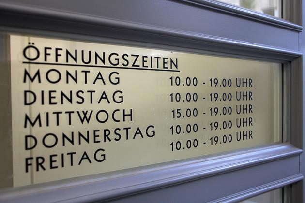 Auf einer Glasscheibe an der Eingangstür stehen die neuen Öffnungszeiten der Bibliothek Plagwitz