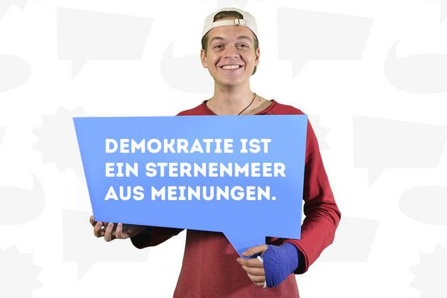 """Ein junger Mann hat sich mit dem Statement """"Demokratie ist ein Sternenmeer aus Meinungen"""", welches auf einer blauen Sprechblase steht, fotografieren lassen."""