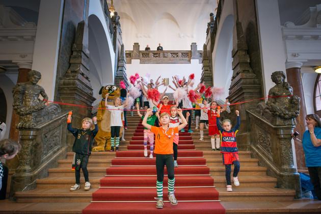 Auf der Treppe zur Oberen Wandelhalle sieht man Jungen und Mädchen in einer Tanzformation, die ihre Arme in die Luft strecken.