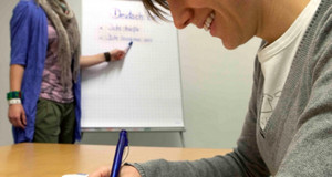 Junge Frau in einem Kurs am Schreibpult sitzend.