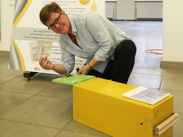Ein gelber Briefkasten liegt auf dem Boden, eine Frau öffnet ihn.