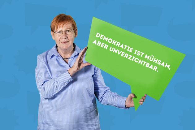 """Die Stadträtin Dr. Ilse Lauter hält ein Schild mit dem Statement """"Demokratie ist mühsam aber unverzichtbar.""""."""