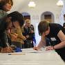 An einem langen Tisch schreiben sich zahlreiche Menschen in Listen ein.