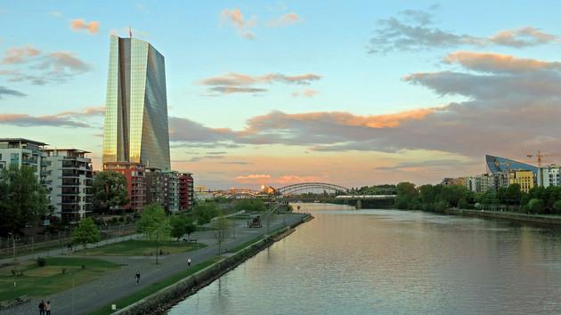 Das Hochhaus der Europäischen Zentralbank in Frankfurt während der Abenddämmerung. Ein Glashochhaus, welches das untergehende Sonnenlicht reflektiert.