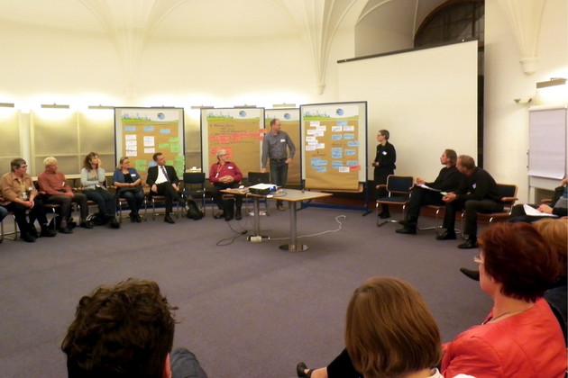 Menschen sitzen in einem Raum und hören Redner bei der Werkstatt Finanzen zu.