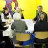 An einem Tisch eine Gruppe junger Männer und Frauen in ein Gespräch vertieft.