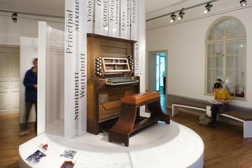 Bild wird vergrößert: auf einer Empore steht ein historisches Klavier, dahinter beschriftete Tafeln