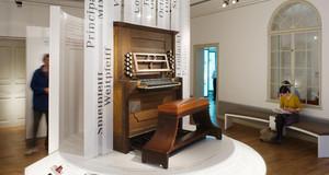auf einer Empore steht ein historisches Klavier, dahinter beschriftete Tafeln