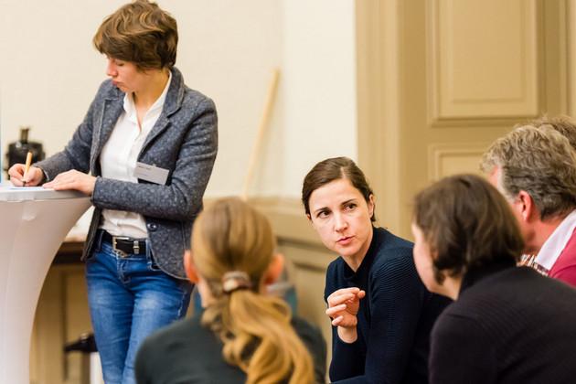 Diskussion in kleiner Runde, eine Frau spricht, die Moderatoren steht an einem Tisch und schreibt