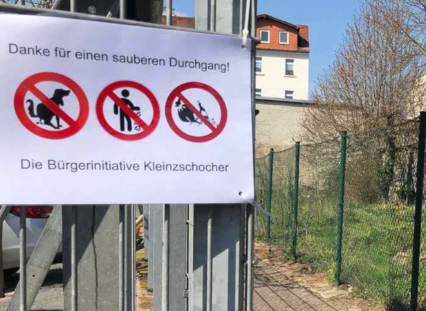 """Kleiner Weg mit einem Hinweisschild: """"Danke für einen sauberen Durchgang""""."""