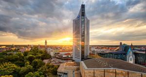 Die Sonne verschwindet am Horizont hinter dem Leipziger City-Hochhaus.