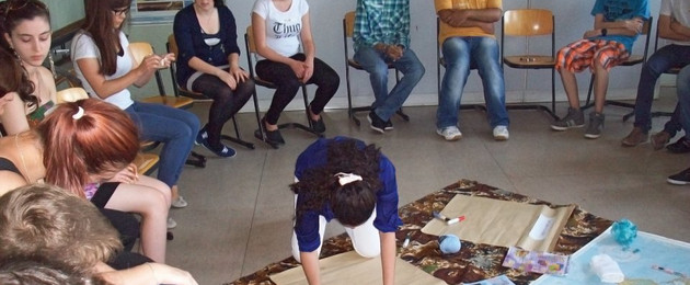 Eine Schulklase sitzt in einem Stuhlkreis und arbeitet zum Thema Fairtrade.