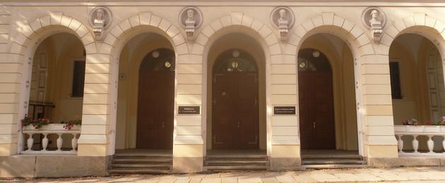 Eingangsbereich einer Schuler mit drei Türen, die von mehreren Torbögen überspannt sind.