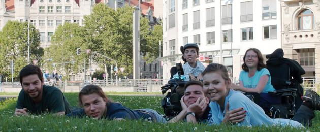 Drei junge Männer und eine Frau liegen im Gras, hinter ihnen sitzen ein Mann und eine Frau im Rollstuhl. Im Hintergrund ist das Neue Rathaus zu sehen.