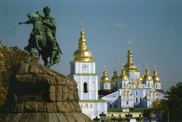 Reiterstatue welche Bogdan Chmelnizki darstellt und Blick auf blau-weiße Sophienkathedrale mit goldenen Turmhauben
