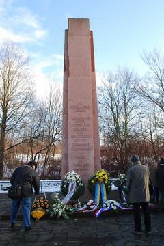 Bild wird vergrößert: Ein steinerner Obelisk, vor dem Menschen Blumenkränze ablegen