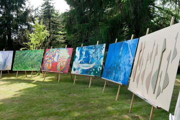 Bild wird vergrößert: Galerie mit großformatigen Bildern auf Staffeleien im Freien
