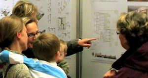 Menschen vor einer Planauslegung, schauen sich die Pläne an und diskutieren miteinander