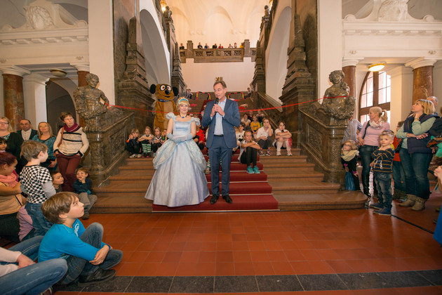 Umringt von großen und kleinen Gästen des Familienspielefestes begrüßt der Oberbürgermeister auf der Treppe zur Oberen Wandelhalle die Anwesenden. An seiner Seite eine Prinzessin in einem hellblauen Kleid.
