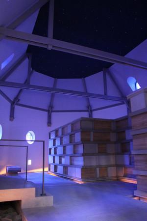 Ein blau beleuchteter Raum mit mehreren Urnenkammern aus Holz und Stein