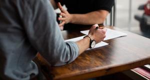 Nahaufnahme auf die Arme zweier Personen, die sich an einem Tisch gegenübersitzen. Einer hält einen Stift fest, vor ihm liegt ein Blatt Papier. Der andere im Hintergrund gestikuliert.