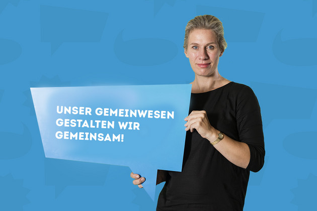 """Die Stadträtin Katharina Krefft hält ein Schild mit dem Statement """"Unser Gemeinwesen gestalten wir gemeinsam!""""."""