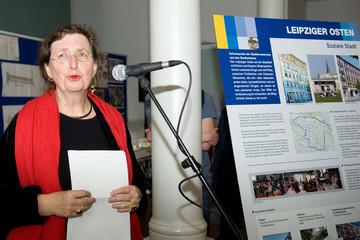Bild wird vergrößert: Die Baubürgermeisterin steht vor einem Mikrophon mit einem Blatt Papier in den Händen. Neben ihr eine steht eine Infotafel zum Leipziger Osten.