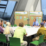 ca. 10 Menschen sitzen in einer Arbeitsgruppe und diskutieren miteinander