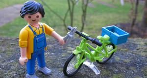 Playmobilfigur mit gelbem Oberteil und Blaumann repariert ein grünes Fahrrad.