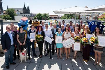 Bild wird vergrößert: Eine Gruppe Menschen steht auf einer Dachterasse und lächelt in die Kamera. Einige in der ersten Reihe haöten Urkunden und Blumensträuße.