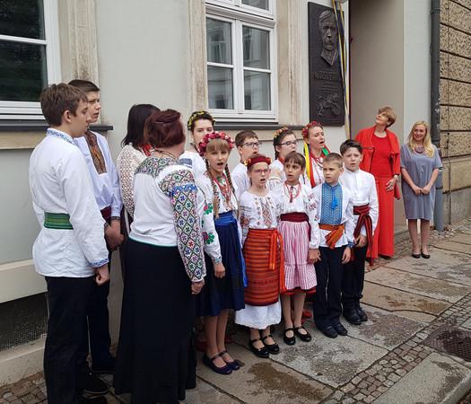 Vor einer grauen Hauswand steht ein Kinderchor in traditioneller ukrainischer Kleidung und singt. Die Mädchen mit bunten Blumenkränzen auf dem Kopf und Schleifen im Haar. An der Hauswand ist eine bronzene Gedenkplatte zu sehen.