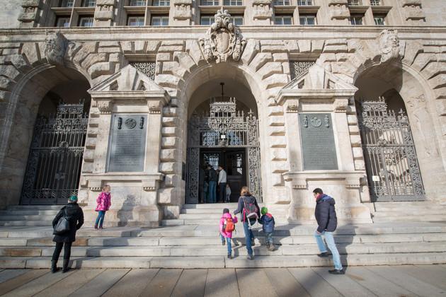 Man sieht die Treppe und den Eingang zum Neuen Rathaus. Eine Mutter hält in der Bildmitte ihre beiden Kinder an der Hand und steigt die Treppen empor. Mehrere Personen sind im Torbogen zu erkennen und im Begriff, das Rathaus zu betreten.