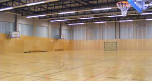 Sporthalle Radrennbahn Innenansicht mit mehreren Basketballkörben an den Wänden.