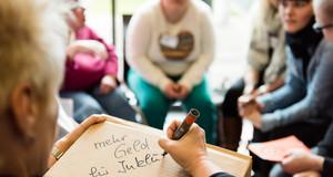 """Gruppe von Menschen sitzt zusammen. Einer schreibt auf einen Block """"mehr Geld für Inklusion"""""""