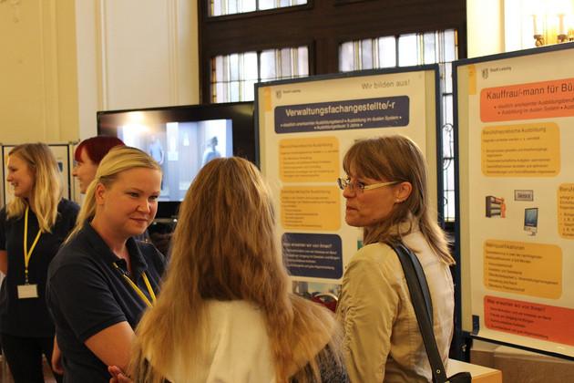 Drei Frauen stehen zusammen und reden miteinander. Dahinter sind Tafeln mit Informationen zum Beruf Verwaltungsfachangestelle/-r.